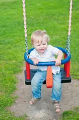 Cute baby boy playing on swing