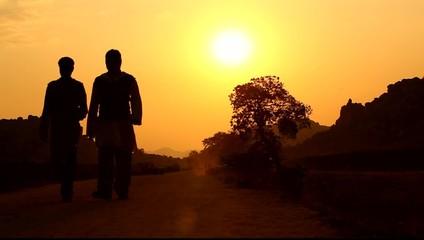 people silhouette on village road