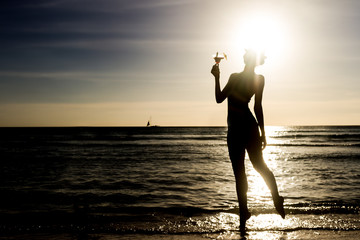silhouette of young woman with glass of tropical cocktail on sun