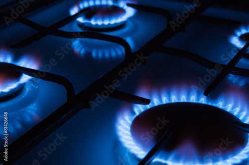 Blue flames of gas burning from a kitchen gas stove - 81426648