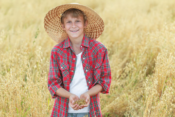 Portrait of smiling farm boy is with oat seeds in cupped palms