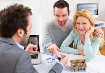 Real estate agent present project on tablet to a young couple