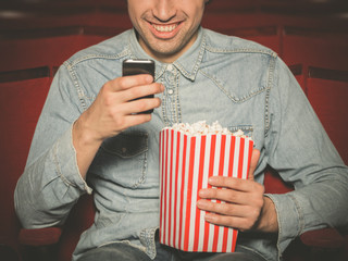 Young man using his phone at the cinema