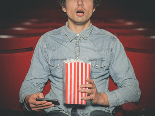 Man in cinema watching movie and using his phone