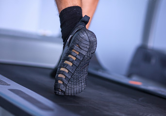 Close-up of man legs in sneakers on treadmill