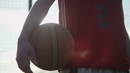 Slow motion basketball player holding a ball outdoors