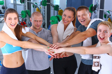 People at the gym putting hands together