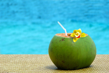 Fresh coconut juice with a drinking straw by the swimming pool