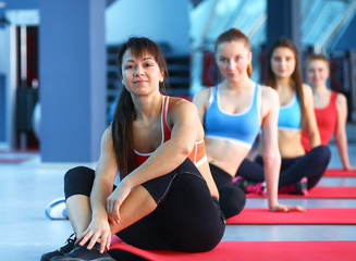 Sporty people sitting on exercise mats at a bright fitness