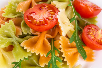 Pasta with arugula tomato and cheese.