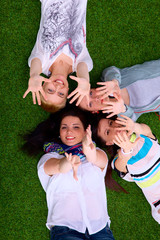 Four young women lying on green grass with hands up