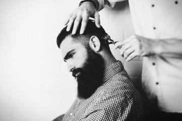 Bearded brutal man in a barber shop