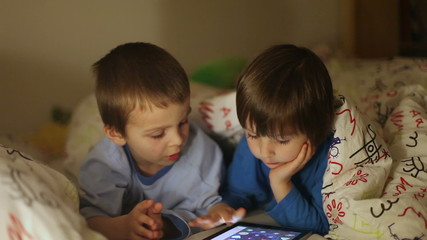 Little brothers playing on tablet in bed at night