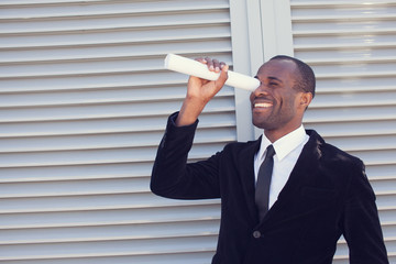 black man searching thru paper spyglass