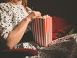Young woman eating popcorn in movie theater - 81431634