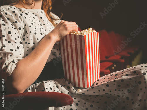 Leinwanddruck Bild Young woman eating popcorn in movie theater