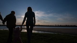 Happy Family Walking on River Bank Silhouettes Sunset