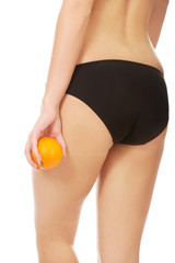 Woman holding orange next to buttocks.