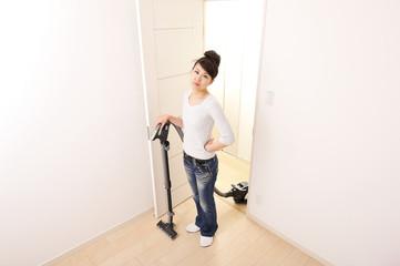 不機嫌な表情をして掃除機をかけている綺麗な日本人女性