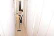 笑顔でマンションの部屋に掃除機をかけているアジア人の綺麗な女性