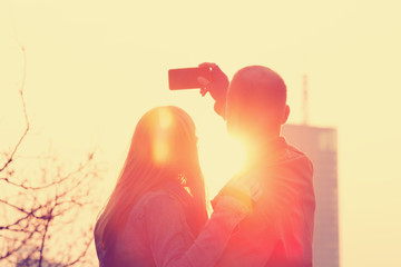 Couple doing selfie outdoors.
