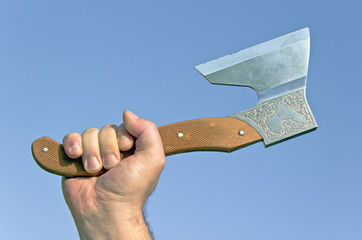 Old ax in hand over blue sky