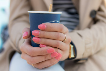 Blue paper Cup of coffee in female hands with pink manicure