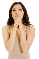 Young woman praying with her hands together.