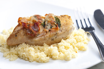 chicken meat on sage baked with bacon and served with couscous