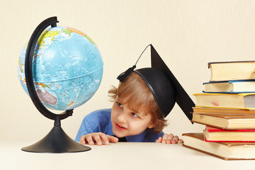 Little smiling professor looks at geographical globe