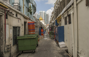 A Back Ally in Singapore. with stacks of crates and wheel bins