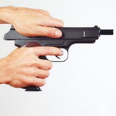 Hands reload handgun on a white background