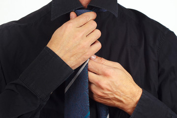 Man straighten his tie over black shirt close up