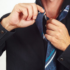 Man unleashes his tie over black shirt close up