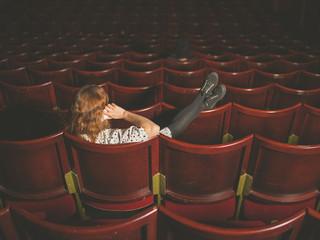 Woman talking on phone in auditorium
