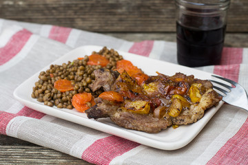 Pork chops with tomatoes on top with lentils and carrots