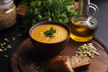Pumpkin and carrot soup, bread and green on the wooden board
