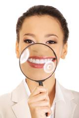 Woman with magnyfying glass on teeth.