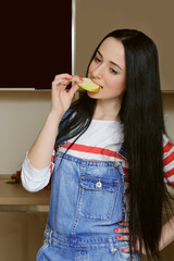 Brunette housewife in blue overalls eating a slice of apple.