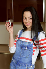 Brunette housewife in blue overalls holding a glass of juice and