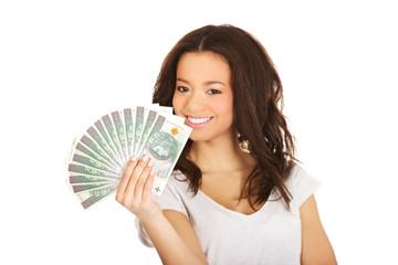African woman holding polish money.