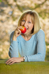 atrractive mature woman is biting in an apple