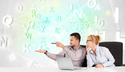 Business people at desk with green word cloud