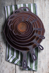 Collection of round rusty cast iron frying pans