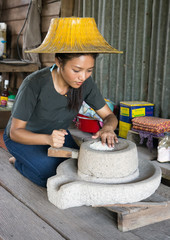 Asian woman mills rice in her home