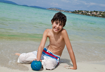 The boy is have fun at the beach with ball