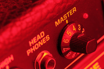 Master volume knob of a guitar amplifier in red light