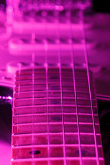 A six string electric guitar with purple light