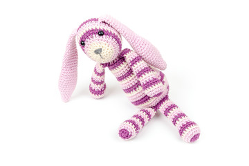 Knitted rabbit toy is sitting isolated on white