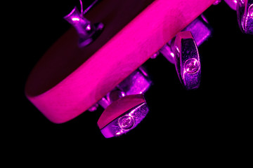 Tuning pegs of a six string electric guitar with purple light